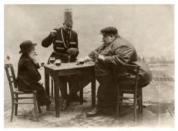 Una cartolina francese con l'uomo più alto, il più basso e il più grasso d'Europa che giocano una partita a carte, 1913