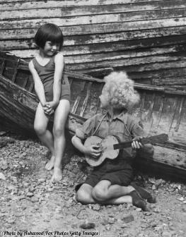 Una bambina ascolta un bambino che suona la chitarra sulla spiaggia di Cliftonville, Kent, 1932