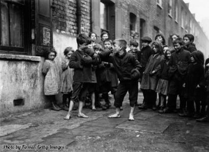 Ragazzi boxano a piedi nudi, mentre i loro amici stanno a guardare, Londra, 1920