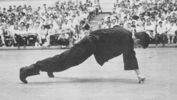 Bruce Lee effettua un push-up con una mano, tenendosi solo sul dito indice e il pollice