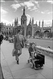 Il professor Stephen Hawking sulla sedia a rotelle davanti a edifici universitari, Cambridge, 1977. Foto di Ian Berry