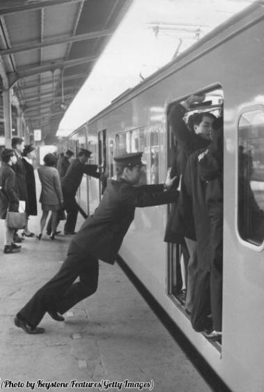 Uomini addetti a spingere la gente alla stazione di Shinjuku di Tokyo nelle ore di punta, 1970
