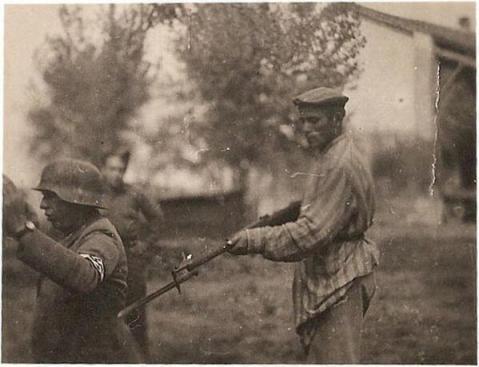 Un uomo ebreo liberato punta il fucile su un soldato tedesco alla fine della seconda guerra mondiale
