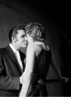 """Per decenni, questa donna era conosciuta come """"date for the day"""", o """"the mystery girl"""", o, il più delle volte, """"The Kiss"""". La foto è stata scattata da Alfred Wertheimer nella tromba delle scale dietro le quinte del Mosque Theatre. Per decenni, nessuno sapeva chi fosse (tranne lei, naturalmente). Wertheimer non ha mai saputo il suo nome. Nel corso degli anni, le donne si sono fatte avanti sostenendo che erano quella ragazza, ma le loro affermazioni sono state sempre smentite."""