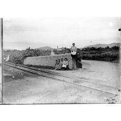 Giulio Pili - Campidano, Gruppo davanti alla ferrovia con sfondo di paese