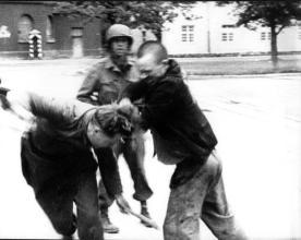 Un prigioniero ebreo liberato esprime la sua rabbia e picchia una guardia tedesca dopo la liberazione del campo di concentramento di Dachau