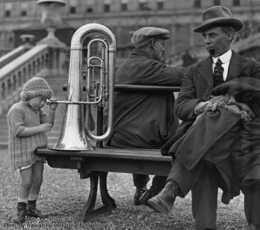 Una bambina guarda all'interno di una tuba al National Festival of the Bands, Londra, 1923