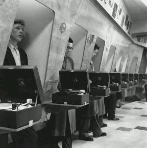 I clienti in un negozio di musica ascoltano le ultime uscite discografiche in cabine di ascolto insonorizzate. Londra, 1955