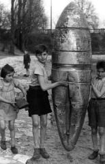 Bambini giocano con il guscio di una bomba sganciata. Berlino, seconda guerra mondiale