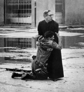 Un sacerdote tiene un soldato morente mentre i proiettili vengono sparati intorno a loro. Venezuela, 1962