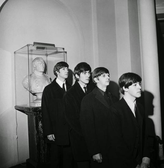 I Beatles in posa con un busto di Napoleone, Parigi 1964. Fotografia di Harry Benson