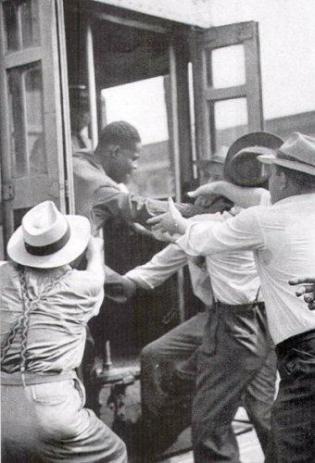 Un uomo di colore è tirato fuori una macchina per strada da uomini bianchi, 1943