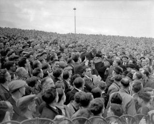 Un giovane tifoso del Chelsea passa sopra la folla verso la parte anteriore per una migliore vista in una partita contro l'Arsenal. 1947