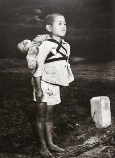 Bambino giapponese sull'attenti, con suo fratello morto sulle spalle, Nagasaki, 1945