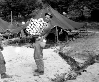 Marine Cpl. RL Quisenberry porta un sacco di birra in Corea, 25 luglio 1951