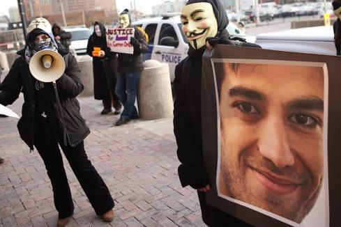 I membri del gruppo Anonymous protestano mostrando una foto di Aaron Swartz