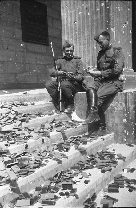 Soldati russi sui gradini della Cancelleria del Reich a guardare medaglie tedesche che non sarebbe mai state assegnate. Maggio 1945