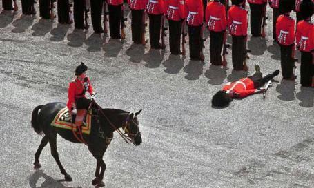 Una guardia della Regina cade a terra mentre Elisabetta II passa a cavallo durante una parata. 1970