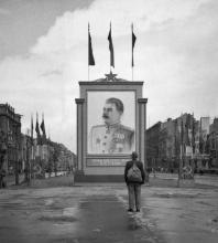 Un civile tedesco guarda un manifesto di Stalin posto di recente sulla Unter-den-Linden di Berlino 1945
