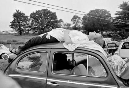 Una ragazza fa un sonnellino nella cappotta della sua auto, prima di raggiungere il festival di musica a Woodstock, N. Y., 16 agosto 1969