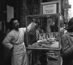 Un ragazzo che vende la pizza in un mercato per strada a Napoli, Italia, nel 1953