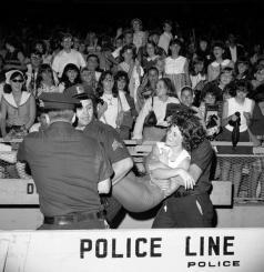 Ragazza sopraffatta dall'emozione viene portata via dalla polizia al concerto dei Beatles allo Shea Stadium, 1965