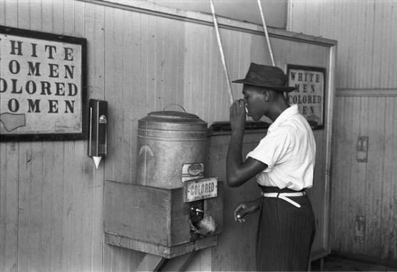 """un afro-americano che beve da una fontanella per """"colorati"""" negli USA"""
