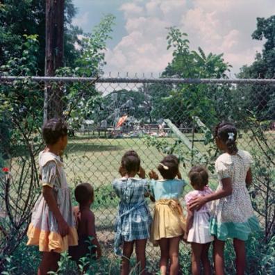 Bambini neri guardano i bambini bianchi giocare in un parco solo per bianchi, 1956. Fotografia di Gordon Parks