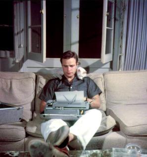 Marlon Brando scrive in compagnia del suo gatto nel 1954