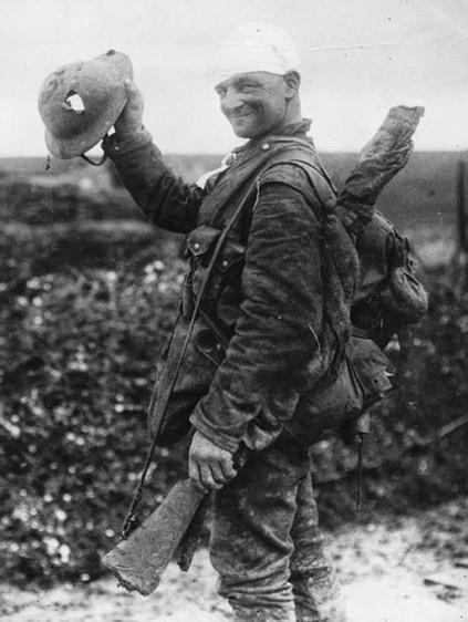 Un soldato britannico nel 1918, è felice perché il suo casco ha subito la maggior parte dei danni