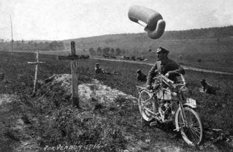 Un pallone da osservazione in aria mentre una staffetta si ferma accanto a delle lapidi durante la prima guerra mondiale