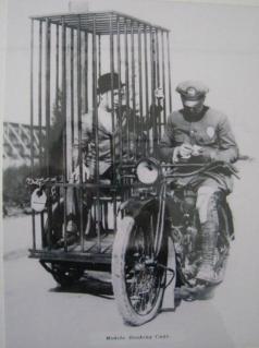 Un agente di polizia su una Harley e una cella di detenzione mobile vecchio stile 1921