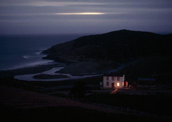 La casa di un pescatore solitario veglia sulla tranquilla baia di Placentia nel Newfoundland, Canada 1974