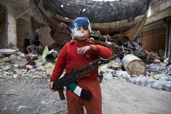 Ahmed, otto anni, figlio di un combattente ribelle siriano, fuma e tiene un AK-47 ad Aleppo By Sebastiano Tomada