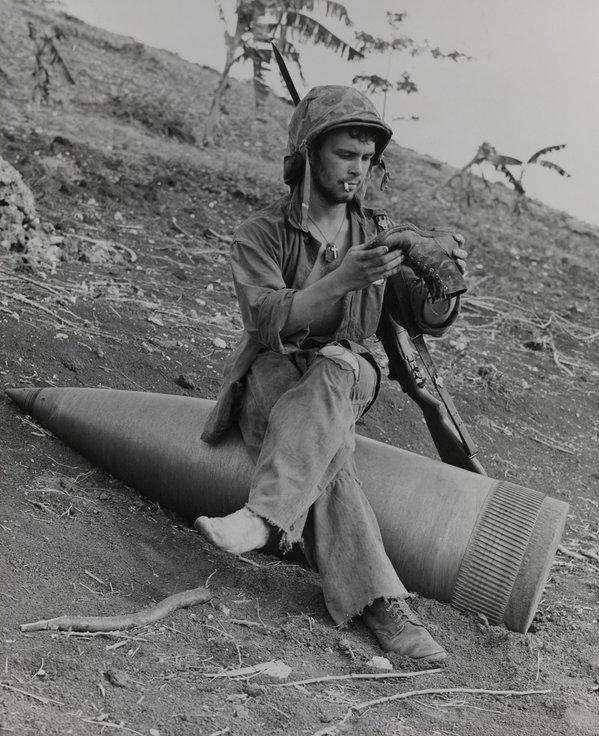 Marine riposa su una bomba inesplosa durante la seconda guerra mondiale