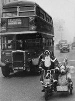 Babbo Natale guida una moto davanti a un autobus per Oxford Street, a Londra, con i regali sul sidecar, 1949