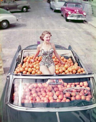 Modella di costumi da bagno in una Cadillac piena di arance, 1951. Foto di Douglas Jones