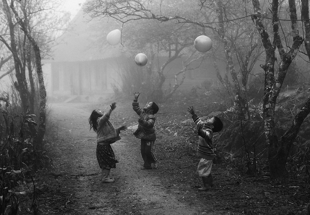 """H'Mong minority children were playing with their balloons on a foggy day in Moc Chau - Ha Giang province, Vietnam. Shooting time Jan 2012."""" (© Vo Anh Kiet/National Geographic Traveler Photo Contes"""