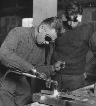 Un uomo reduce dalla prima guerra mondiale con un braccio amputato dotato di un braccio per la saldatura