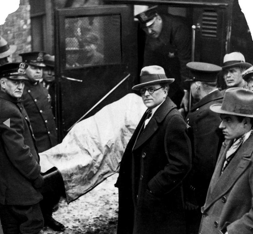 Il corpo di una delle sette vittime è posto in un'ambulanza col medico legale Herman N. Bundesen, al centro. - Chicago Tribune historical photo
