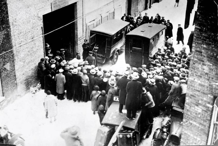 La folla si raduna nel vicolo dietro 2122 N. Clark St., mentre la polizia rimuove le vittime della strage del giorno di San Valentino. - Chicago Tribune historical photo