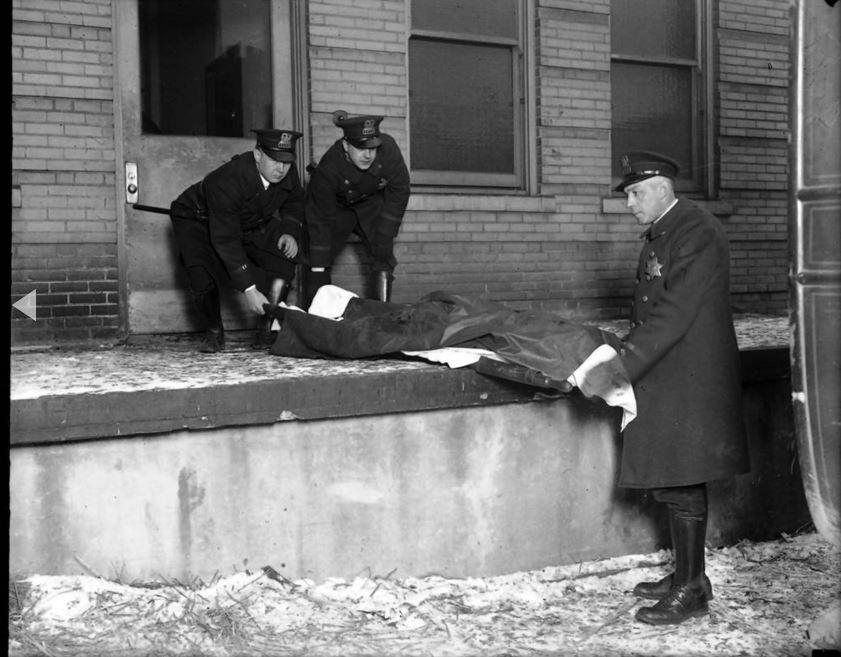 """Il corpo di Albert Kachellek, alias """"James Clark"""", viene rimosso dal all'obitorio della contea il 15 febbraio, 1929. Clark era il fratello-in-law del capobanda George """"Bugs"""" Moran esi diceva avesse la reputazione da spietato assassino. - Chicago Tribune historical photo"""