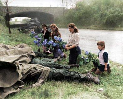 Donne liberate da un campo di concentramento mettono fiori sui cadaveri di 4 soldati americani, 1945. colorato da Malakon su reddit