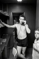 Elvis Presley al telefono in casa dei genitori. A destra il cugino Billy Smith