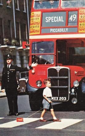 Un autobus si ferma per un ragazzo che attraversa la strada, Londra, c. 1960