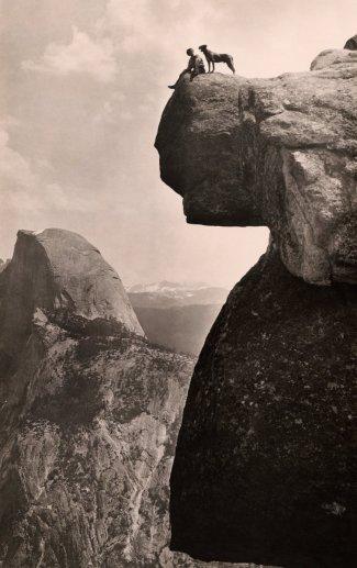 Un uomo e il suo cane sulla roccia a strapiombo al Yosemite National Park, 1924. Fotografia da Educational-Bruce