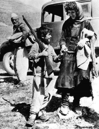 Un bambino albanese con un fucile mentre fugge in Jugoslavia con la madre dopo l'invasione italiana dell'Albania, 1939