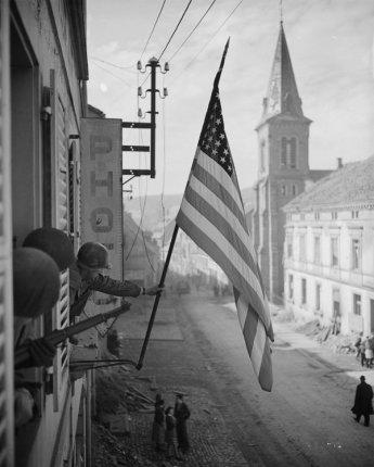 Cap. Thomas H. Garahan alza la bandiera degli Stati Uniti da una finestra a Bitche, Francia 1945