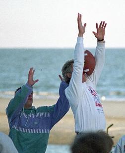 Il presidente Bill Clinton manca la palla mentre gioca a calcio sulla spiaggia in Carolina del Sud, 1993