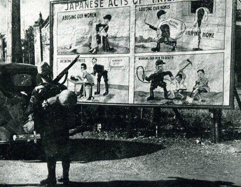 Un soldato giapponese guarda i cartelli di propaganda degli Stati Uniti nelle Filippine, 1943